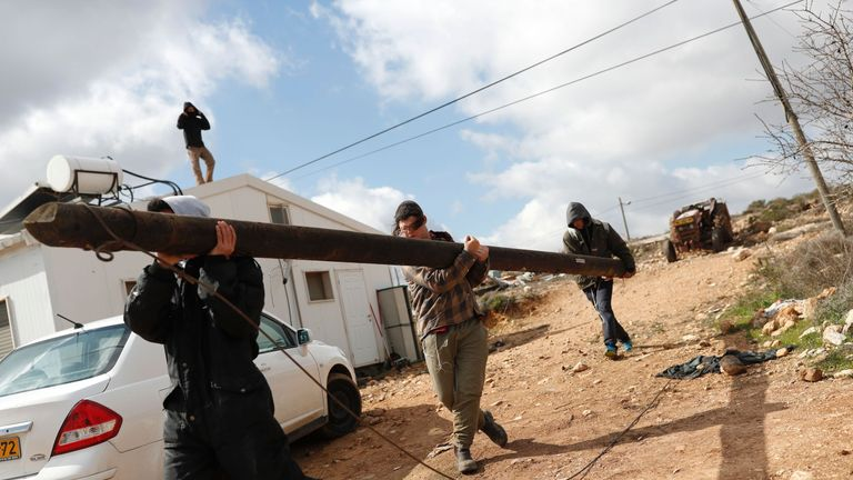 Israeli settlers carry an electricity pole
