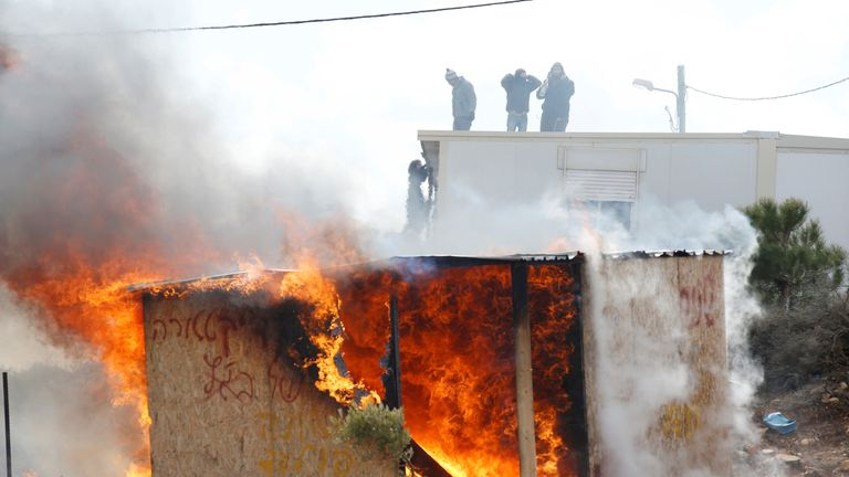 Protesters stand on a roof as a shed burns