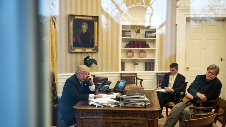 President Donald Trump speaks on the phone with Australian Prime Minister Malcolm Turnbull in the Oval Office of the White House, January 28, 2017 in Washington, DC. Also pictured at right, National Security Advisor Michael Flynn and White House Chief Strategist Steve Bannon. On Saturday, President Trump is making several phone calls with world leaders from Japan, Germany, Russia, France and Australia