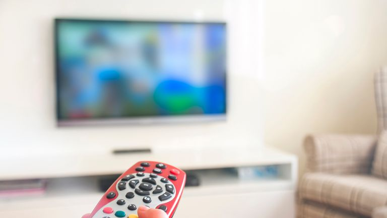 Sky remote in hand as someone watches TV