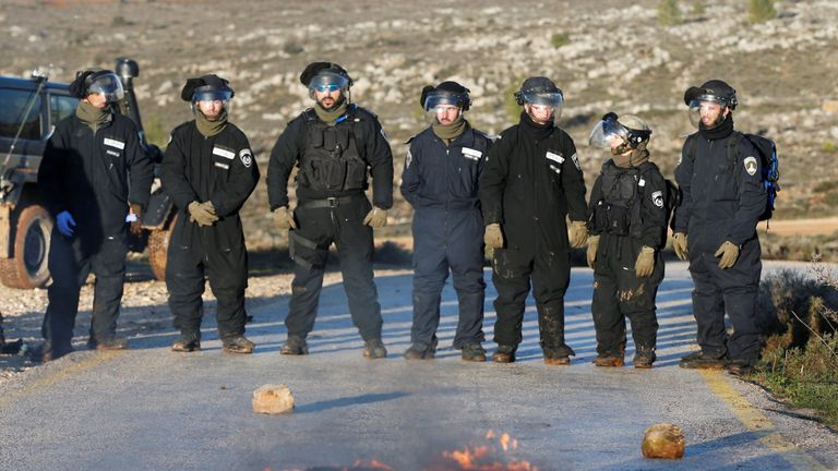 Israeli policemen stand next to a burning tyre on a road