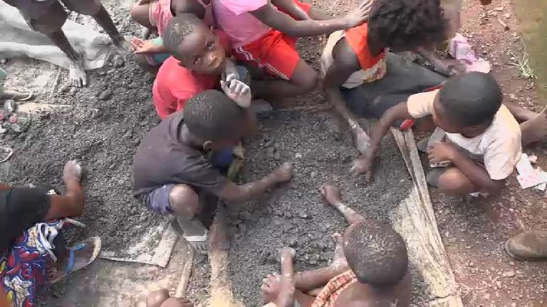 Young children sift through cobalt without protective gloves