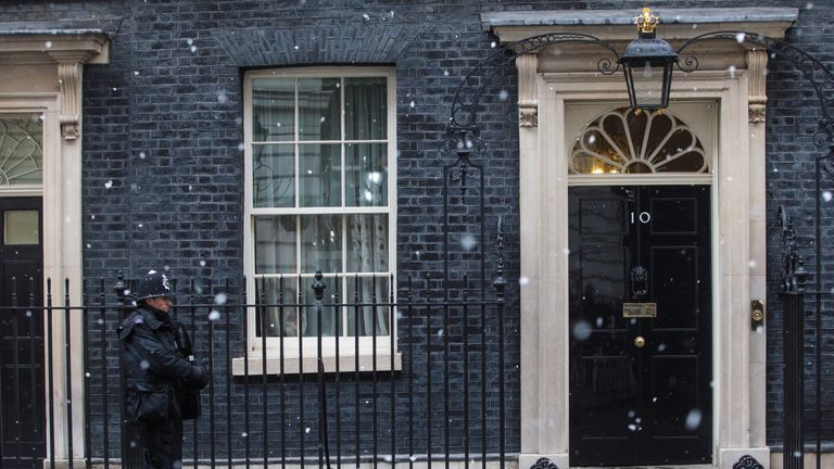 A police officer is pictured standing by Number 10 Downing Street in the snow on February 11, 2017 in London, England