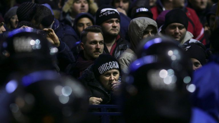 Protesters face Romanian police during a demonstration in Bucharest