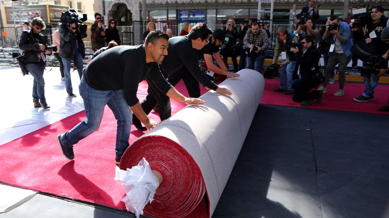 Workers roll out the red carpet ahead of the Academy Awards in Hollywood