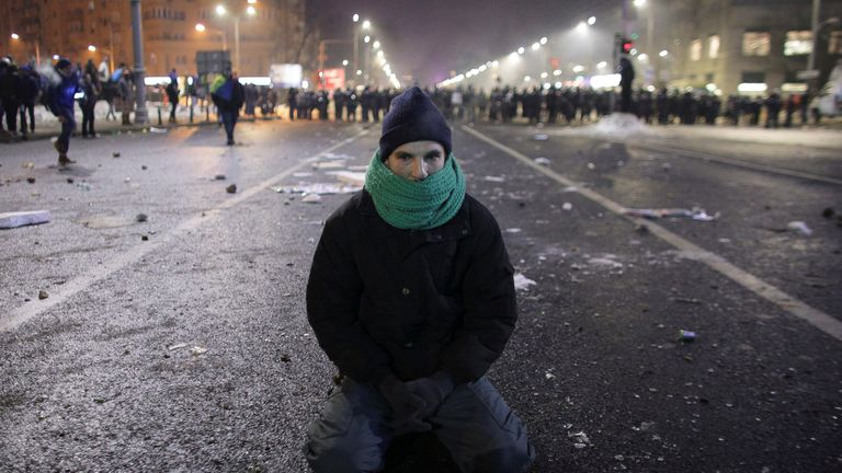 Protestor sits on the ground following scuffles between protestors and Romanian police at a demonstration in Bucharest