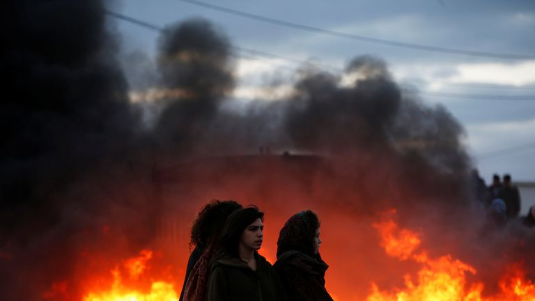 Protesters stand next to fire at the entrance to the Israeli settler outpost of Amona