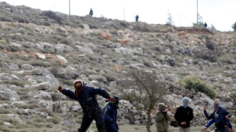 A protestor throws a stone towards Israeli security forces during an eviction of residents