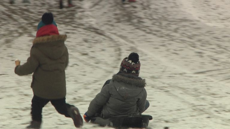 Children play in the snow at a park in Birmingham