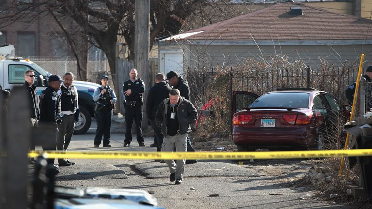 Police look over the bullet-riddled car