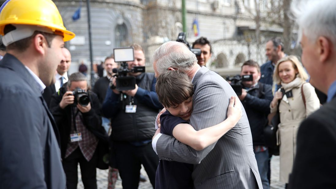 Prince Charles embraces Valentin Blacker during his visit to Bucharest