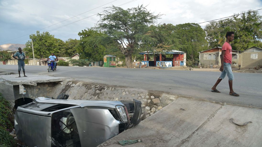 A car damaged by the speeding bus lies on the side of the road in Gonaives