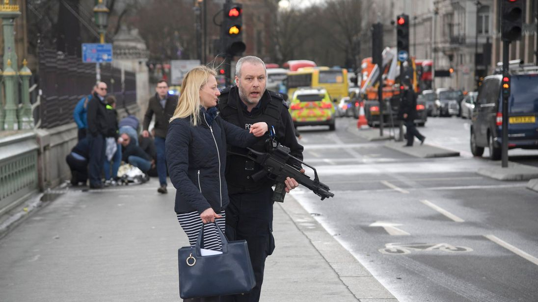 An armed police officer assists a woman after an incident on Westminster Bridge in London