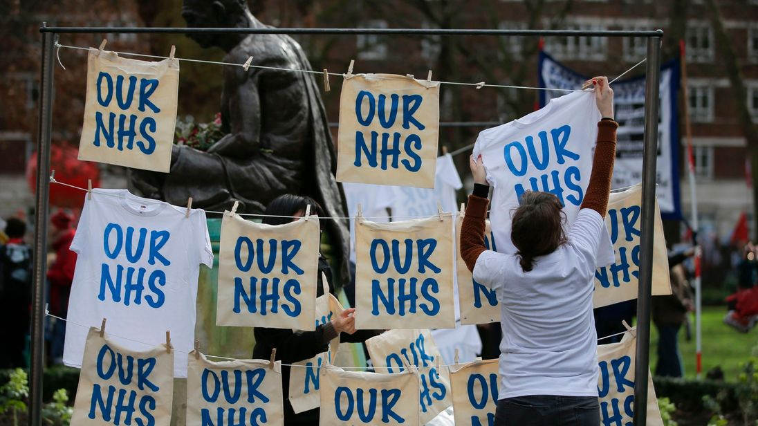 An acticvist pegs up 'Our NHS' signs and T-Shirts during a rally against private companies' involvement in the National Health Service (NHS) and social care services provision and against cuts to NHS funding in central London on March 4, 2017. People gathered to demonstrate at the rally publicised by the People's Assembly Against Austerity to demand a fully and publicly funded NHS and social care service, returned fully to public ownership and provision and to say no to cuts in NHS funding