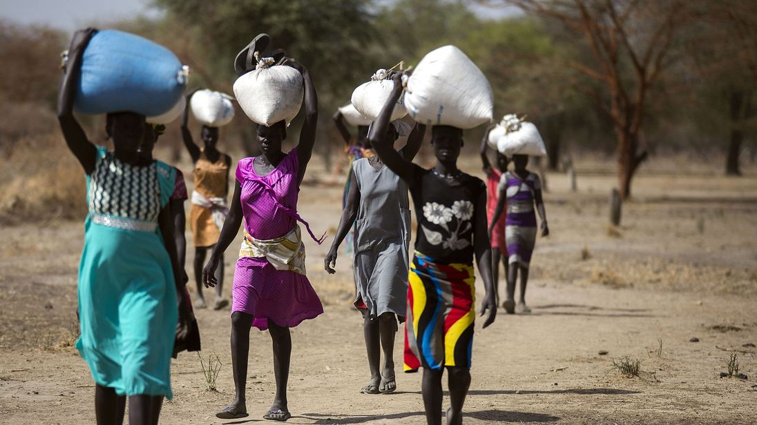 Women carry food in gunny bags from an aid centre in Ngop, South Sudan