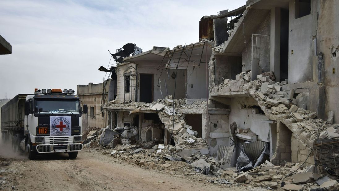 A Red Cross aid truck drives past destroyed buildings in Homs