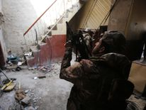 Iraqi forces, consisting of the Iraqi federal police and the elite Rapid Response Division, secure a building
