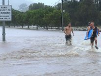 Locals run through floodwaters in the the Gold Coast suburb of Mudgeeraba in Queensland