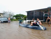 People paddle in a kayak after flood waters entered their back yard in Murwillumbah