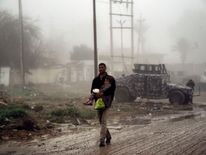 An Iraqi man carries his child as they flee west Mosul