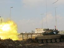 A tank of Iraqi rapid response forces fires against Islamic State militants at the Bab al-Tob area