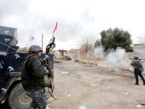 Federal police members fire their weapons during a battle against Islamic State militants