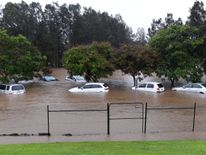 Cars sit submerged after heavy rain associated with Cyclone Debbie hit the Gold Coast suburb of Robina in Queensland, Australia