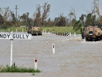 Army vehicles drive through floodwaters near the Queensland town of Bowen