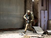 A member of the Iraqi forces, consisting of the Iraqi federal police and the elite Rapid Response Division, runs for cover