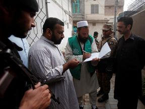 A census checker takes details from a resident of Peshawar, Pakistan