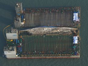 An aerial image of the damaged Sewol ferry between two barges after being raised during a salvage operation at sea off the southwestern island of Jindo on March 23, 2017.