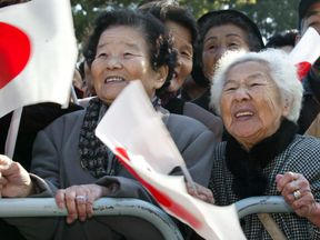 Elderly Japanese women wave national flags as Emperor Akihito makes a special appearance on his 69th birthday at the Imperial Palace in Tokyo, December 23, 2002