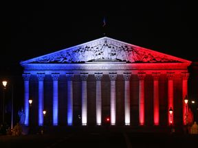 France's National Assembly is lit up in the colours of the French flag
