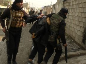 An Iraqi SWAT team grabs a suspected IS militant in east Mosul