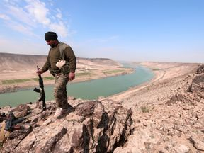 A Syrian Democratic Forces fighter poses for a picture near Euphrates River, north of Raqqa city