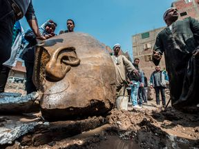 Workers at the site of a discovery of a statue, thought to be pharaoh Ramses II, in Cairo