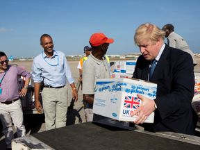 Britain's Foreign Secretary Boris Johnson helps to load supplies for treating malnourished children affected by the severe drought in Somalia onto a cargo plane at Mogadishu International Airport in Mogadishu, Somalia March 15, 2017