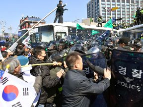 Protesters supporting South Korean President Park Geun-hye clash with riot policemen near the Constitutional Court in Seoul, South Korea, in this photo taken by Kyodo on March 10, 2017. Pic: Kyodo/via Reuters
