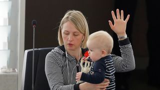 Swedish Member European Parliament Jytte Guteland holds her baby as she takes part in a voting session in Strasbourg