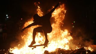 A man practices a skateboarding move in front of a fire set by protestors following an anti-government demonstration in Rio, Brazil