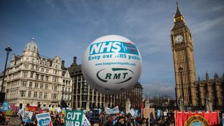 Protesters holding placards gather during a demonstration in support of the NHS