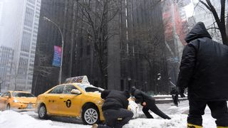 Men try to push a cab stuck in the snow on a street in New York during Storm Stella.