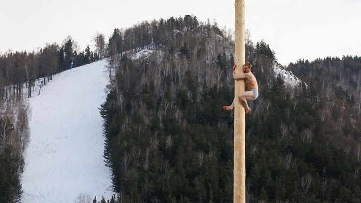 A man tries to get a prize from a pole during an celebration in Krasnoyarsk last month