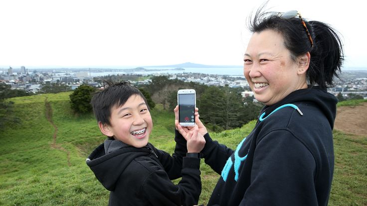 Elaine Chung (R) says Pokemon Go is a great way to bond with her son Samuel (L) as they search on the summit of Mount Eden on July 13, 2016 in Auckland, New Zealand