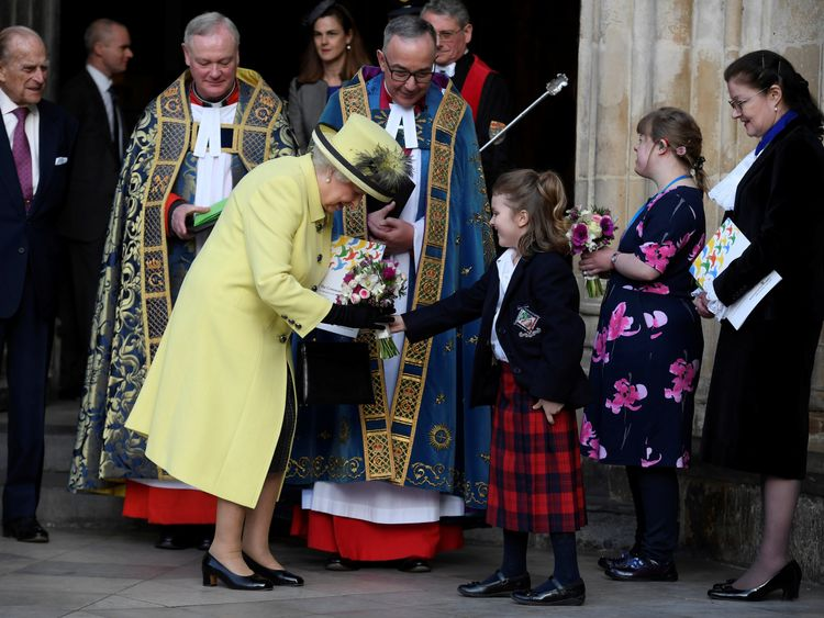Britain's Queen Elizabeth receives flowers from a schoolgirl following a Commonwealth Day service at Westminster Abbey in London