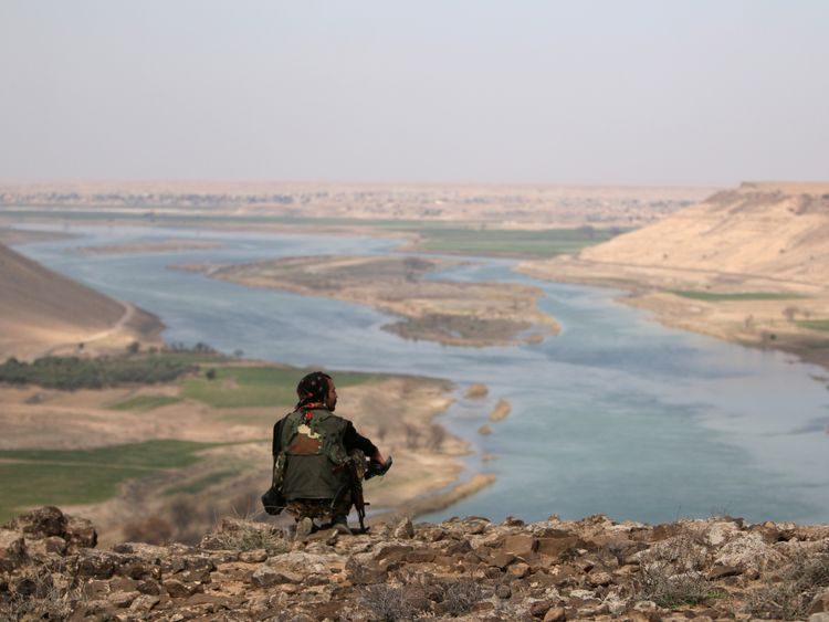 A Syrian Democratic Forces fighter rests while looking over the Euphrates River, north of Raqqa city