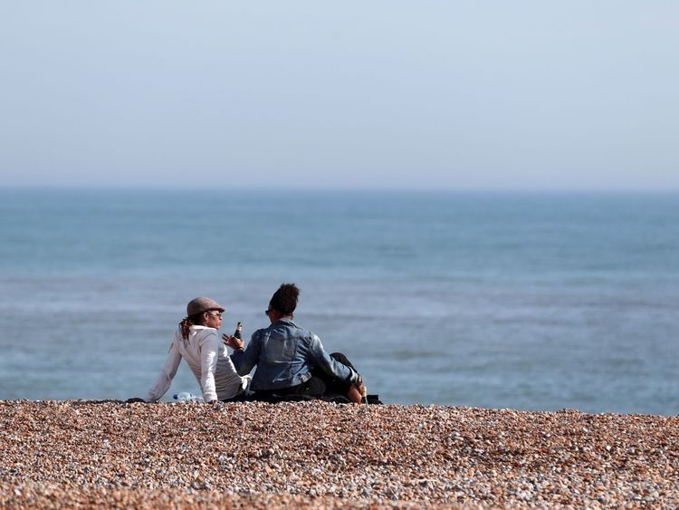 People enjoy the sunshine on the beach in Hastings, East Sussex, on a day when temperatures in the south east of England were expected to be higher than the seasonal average and reach 22C
