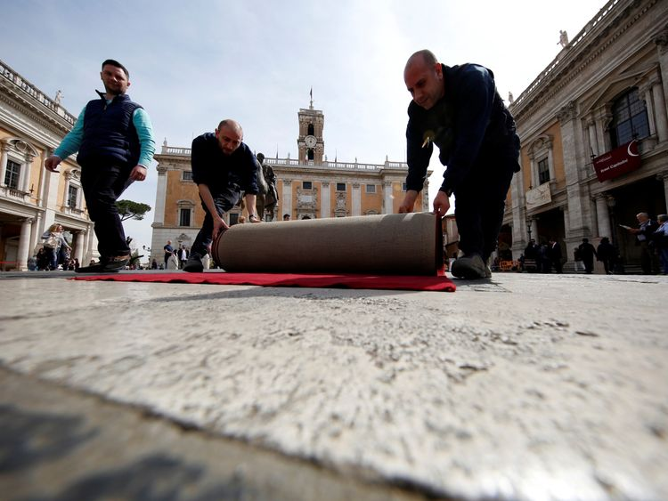 """Workers lay a red carpet in front of the city hall """"Campidoglio"""" (the Capitoline hill) as preparation for the meeting of EU leaders on the 60th anniversary of the Treaty of Rome"""