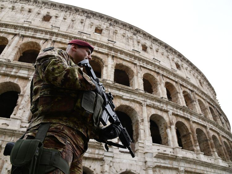 A soldier patrols near the ancient Colosseum in Rome ahead of an EU summit