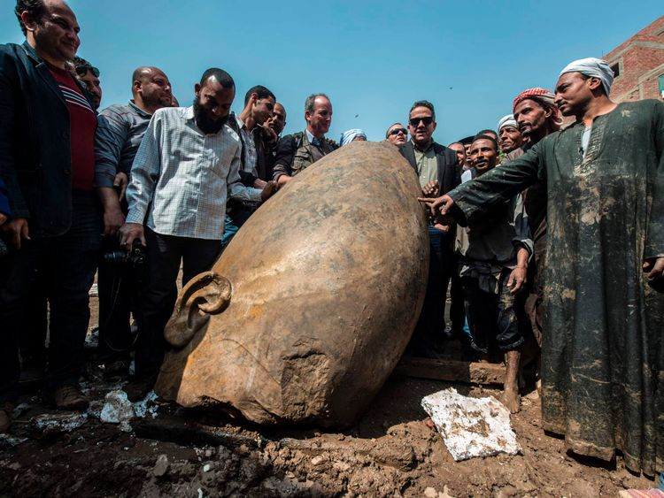 Egyptian minister of antiquates Khaled el-Anani posing with the head of a statue found in a Cairo slum